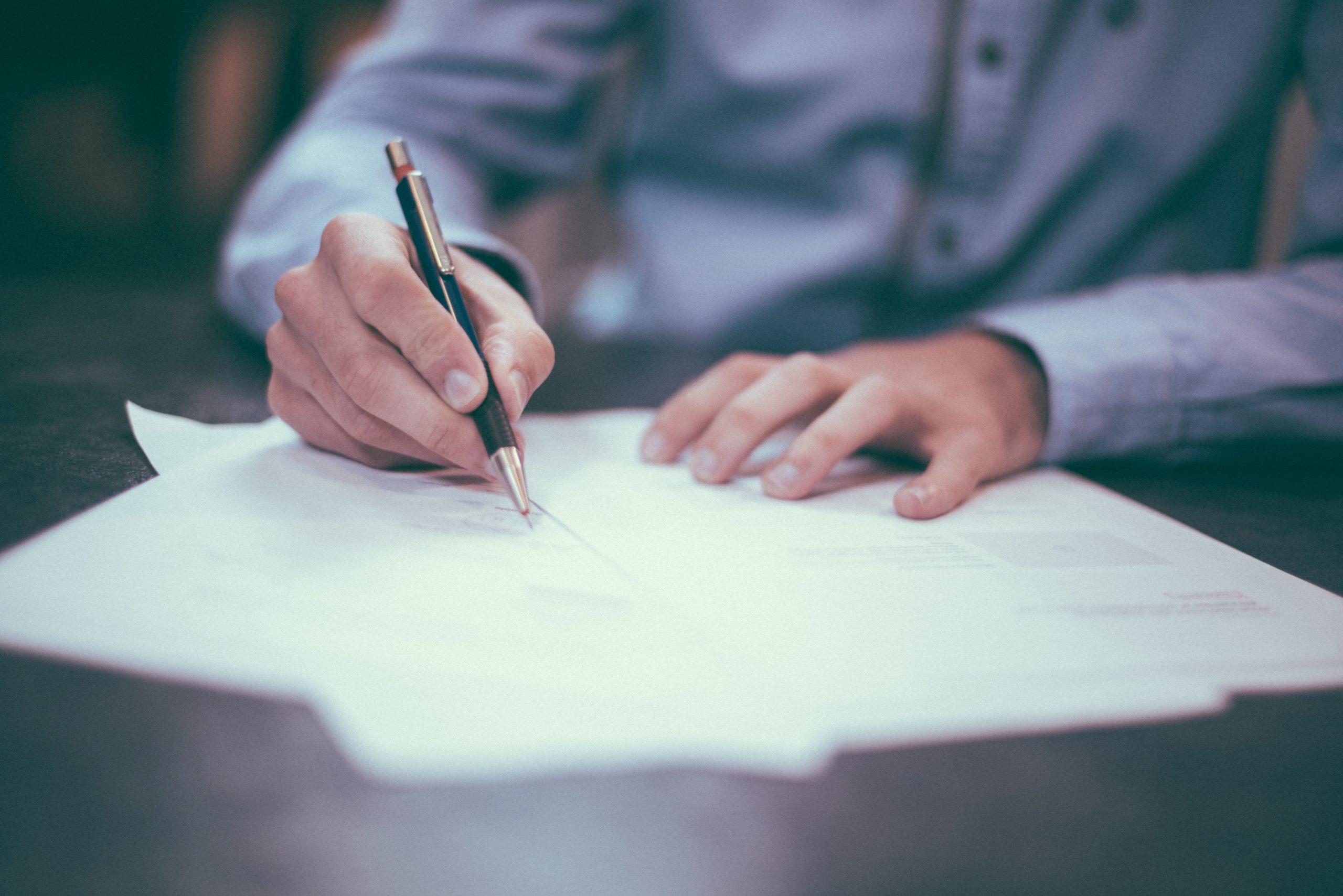 ペンを用いて紙に記入する男性